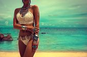 Slim and tanned girl in trendy Boho style on the beach. Girl in a white knit swimsuit with silver jewelry . Bracelets and rings with turquoise stones. poster