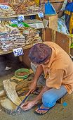 The seller cuts the dried fish into the small cubes at his stall in Fose Market Pettah Colombo Sri Lanka. poster