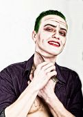 guy with crazy joker face holding knife, green hair and idiotic smike. carnaval costume. poster