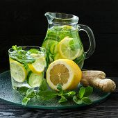 Water Sassi. Vitaminized cleansing water with lemon cucumber ginger mint and ice in a pitcher and a glass on a metal tray. The concept of dietary and vegetarian nutrition. Square image poster