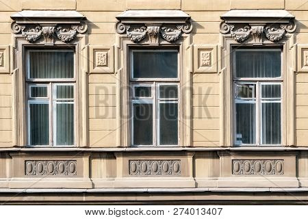 Three rectangular windows on the background of a beige wall with a cornice in the form of a bas-relief. From the series window of Saint-Petersburg. poster