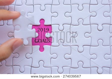 Woman Hand Holding White Jigsaw Puzzle Piece With Words 2019 Goals. Business Resolutions, Success, G