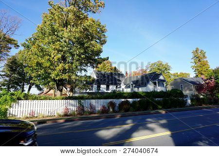 A Large White Summer Cottage, Behind A Stockade Fence, In Bay View, Michigan, During October.