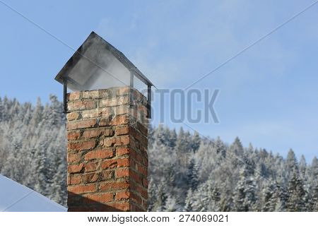 Chimney Pipe On The Background Of Snow-covered Forest And Blue Sky. Stove Heating
