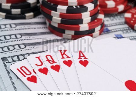 Royal Flush And Poker Chips Are On The Background Of One Hundred Dollar Bills