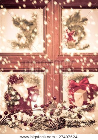 Looking into a festive seasonal Christmas window as snow falls outside