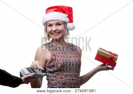 Photo of happy blonde in glasses and Santa hat with gift and man's hand with terminal for bank card