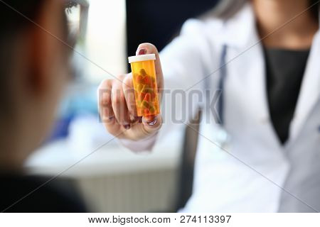 Female Medicine Doctor Hand Hold Jar Of Pills And Write Prescription To Patient At Worktable. Panace