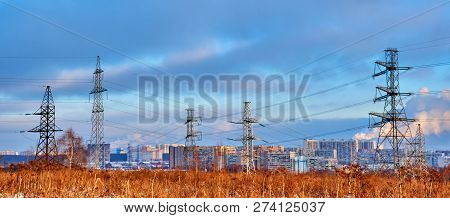 Outskirts of Moscow.In the center of the picture we see the supports of high-voltage power lines, modern houses, roads, smoking pipes. In the foreground are trees without leaves, shrubs, and withered. poster