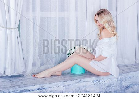 Young Sexy Blonde Woman Is Sitting In A White Shirt Near A Large Window With Box Of  White Roses