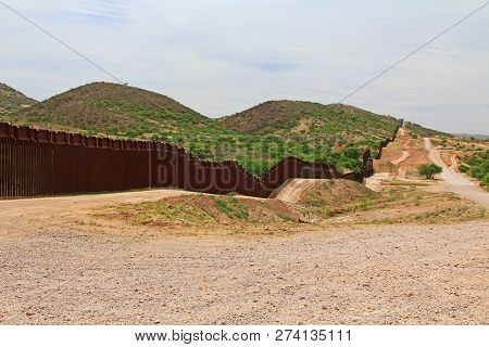 Border Fence Beside A Road Near Nogales, Arizona Separating The United States From Mexico With Borde