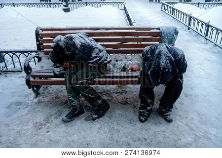 Two Unrecognizable Dirty Homeless Men Or Alcoholics Or Drug Addicts Are Sleeping On Bench In Cold Wi