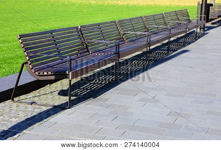 Long Wooden Bench In The City Park