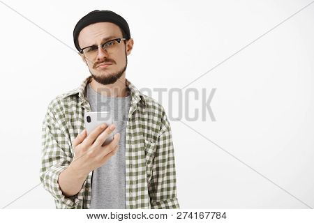 Indifferent Male Young Snob In Glasses And Beanie With Beard Holding Smartphone Smirking And Staring