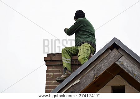Chimney Sweep Man Cleaning Brown Brick Chimney On Building Roof On Clear Sky Background With Copy Sp