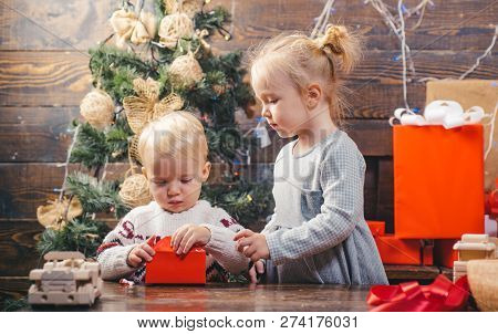 New Year Kids. Portrait Kid With Gift On Wooden Background. Funny Kid Holding Christmas Gift. Merry