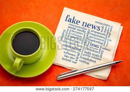fake news word cloud on a napkin with a cup of espresso coffee
