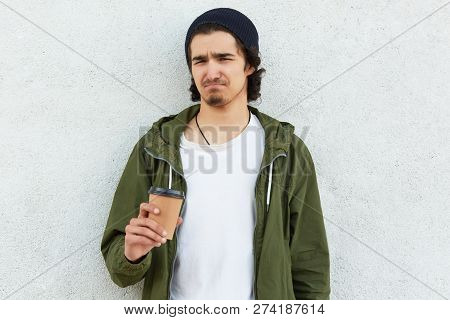 Photo of displeased youngster with discontent facial expression, has curly hair, little beard, carries disposable cup of coffee, dressed in fashionable clothes, isolated over white background. poster