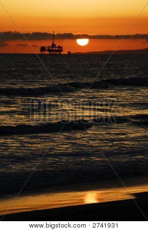 Beach Sunset Over Oil Derrick Off The California Coast.