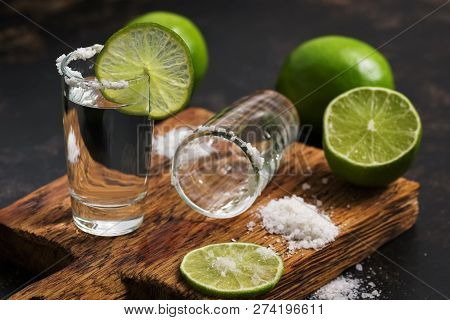 Tequila With Lime Slice And Salt On A Cutting Board. A Drunk Stack Of Tequila Is Empty On A Cutting