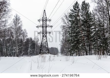 High-voltage Power Line Pylon On A Forest Glade On A Cloudy Day