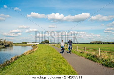 Two Unidentified People Cycle On A Cycle Path At The Top Of A Dike Along A Narrow River At The Dutch