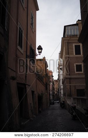 View of a shadowy cobbled street in Rome, Italy, with classic mediterrranean architecture poster