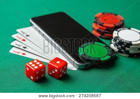 Mobile Phone Casino Online. Mobile Phone And Game Cards With Chips And Dice On A Green Gaming Table.