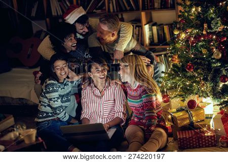 happy friends watching movie on laptop on Christmas eve
