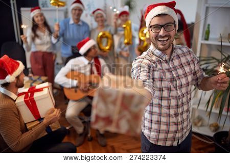 happy business man have fun in Santa hat at Xmas party with his colleagues in office