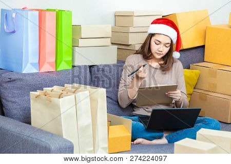 Young Asian Female Entrepreneur Online Seller, Wearing Christmas Hat, Working On Her Online Business