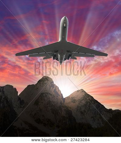 Airliner over the rocky mountains against beautiful sunset. Travel concept.