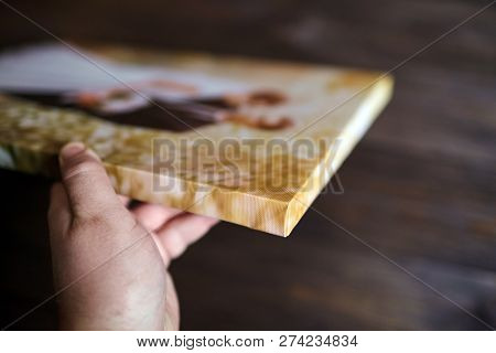 Male Hand Holding A Photography With Gallery Stretch On A Wooden Frame. Printed Wedding Photo On Can