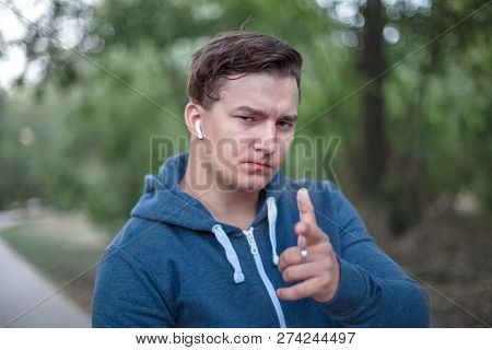 Hey You. Close Up Portrait Of Serious Young Caucasian Man Pointing Finger At You. Park Ourdoors Back