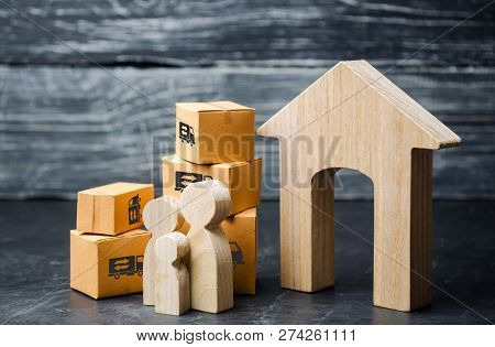 Family And Cardboard Boxes Near The House. The Concept Of Moving To A New Home, Relocation. Moving T