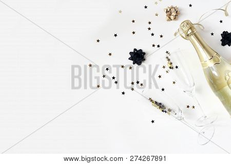 Happy New Year Composition. Champagne Wine Bottle And Glasses With Golden Confetti Stars Isolated On