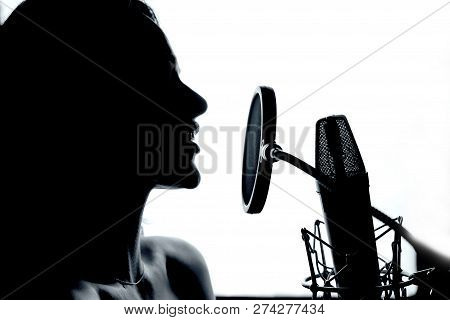 Female Vocalist Performing Music In Front Of The Microphone In The Recording Studio. Profile Of A Wo