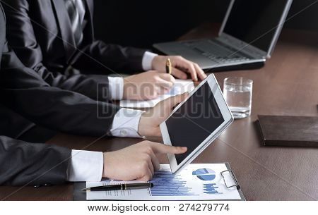 Close Up.businessman Using Digital Tablet To Check Financial Dat