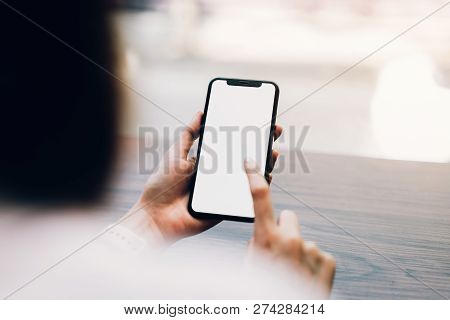 Closeup Of Woman Holding A Smartphone, Mock Up Of Blank Screen. Using Cell Phone On Cafe. Technology