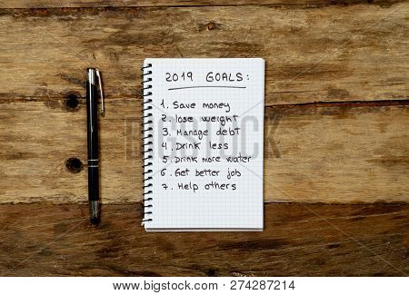 2019 New Year Resolutions List Written On Notebook And Pen On Wood Table In Goals For Happy Life