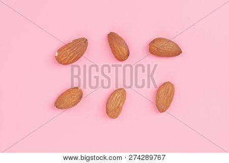 Top View Almond Set On Pink Background, Abstract Background With Almond Pattern. Composition Of Nuts
