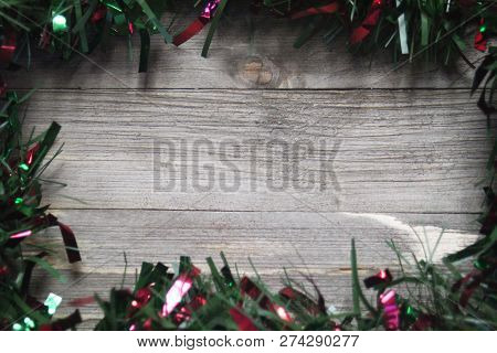 Red And Green Garland Border On A Wood Background