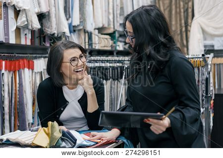 Two women working with interior fabrics digital tablet in showroom for curtains and upholstery fabrics, designer and buyer choosing fabrics in new interior. poster