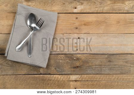 Grey Dishcloth With Fork And Spoon Silverware On Brown Rustic Wooden Plank Table Flat Lay Top View F