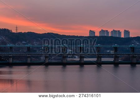 Dam across river with highrise apartment buildings on hill in background with orange hue in overcast sky as the sun sets in the evening. poster