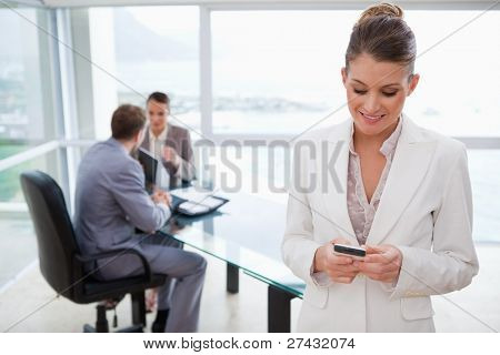 Marketing manager reading text message with her team sitting behind her