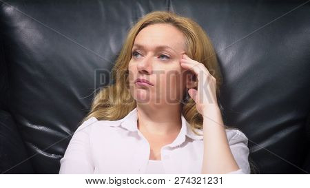 Close-up. An Elegant Woman In A White Suit, Sitting In A Large Black Leather Chair, Thinks About Som