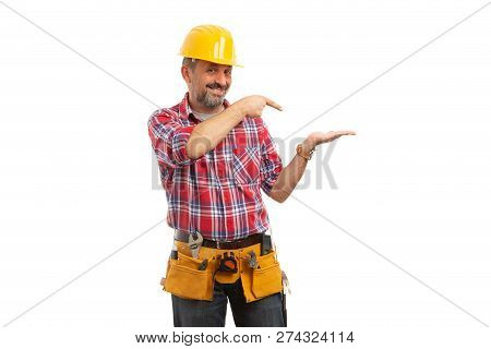 Builder with trustworthy expression presenting blank copyspace in palm isolated on white studio background poster