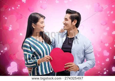 Joyful Asian Couple Embrace And Holding Red Paper Hearts Over Pink Background. Love Concept And Vale