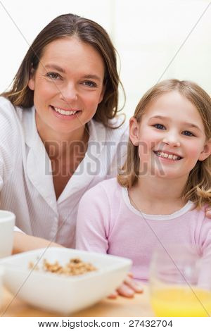 Portrait of a lovely mother and her daughter having breakfast in a kitchen